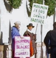 Mormon protestors - 'Mormon Jesus is Devil's brother' and 'Mormons say Blacks are Cursed'